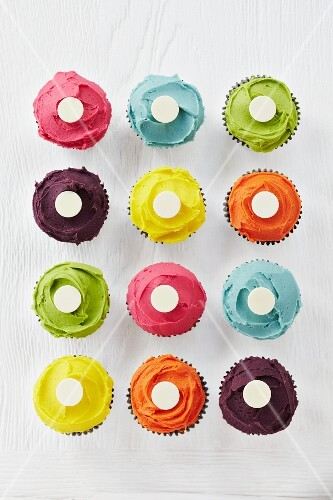 Cupcakes with vibrant icing topped with a white button in the centre (seen from above)