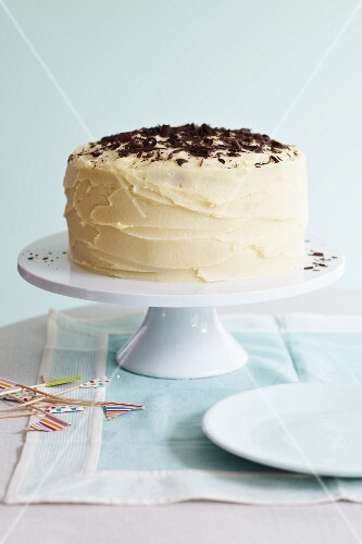 A large celebration cake with white buttercream icing topped with chocolate curls
