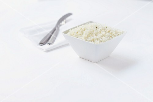 A bowl of rice with cutlery and a napkin next to it