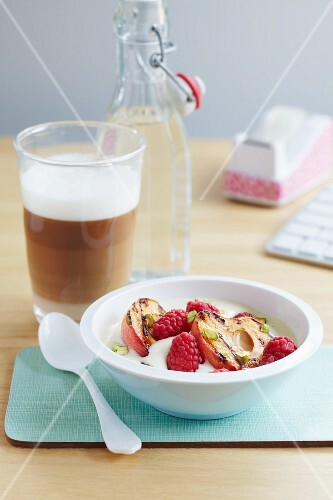 Yoghurt topped with raspberries, grilled apples and pistachios