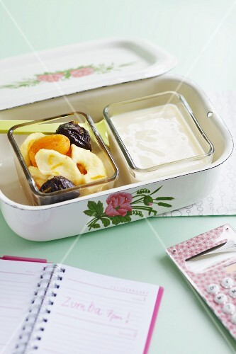 Yoghurt with dried apricots, bananas and plums in a lunch box