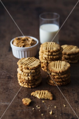 Peanut butter cookies with a glass of milk on a dark wooden surface