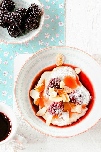 Mini blackberry pancakes with berry sauce and flaked almonds