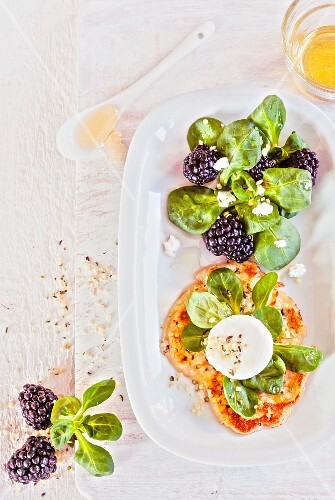 Sesame seed cakes with goat's cream cheese, lamb's lettuce and blackberries