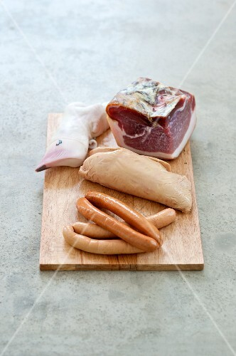 Various types of sausages and goose liver on a chopping board