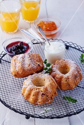 Mini Bundt cakes with icing sugar, cream and jam