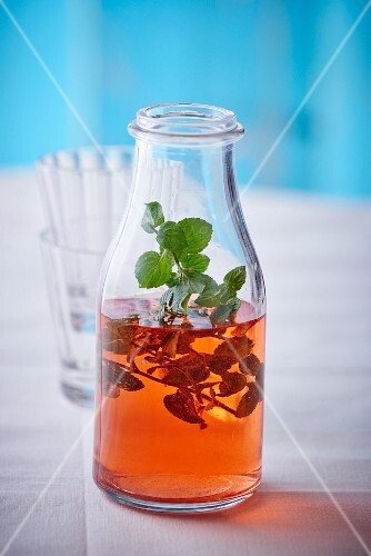 A bottle of strawberry syrup with mint