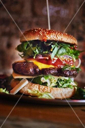 A cheeseburger with ketchup and salad