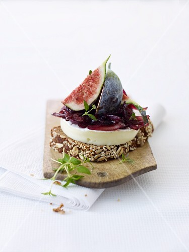A slice of bread topped with brie, figs and onion chutney