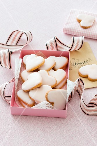 Heart-shaped biscuits with icing sugar in a pink box