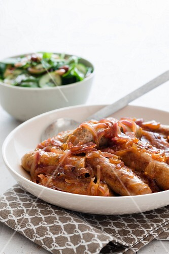 Pork sausages with onions and a spinach and bean salad