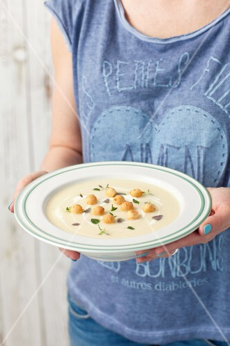 A woman holding a plate of celeriac and potato cream soup with horseradish