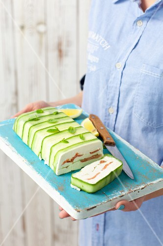 A woman holding a quark and salmon terrine with cucumber on a tray
