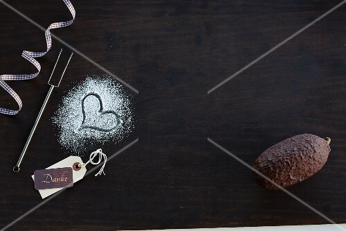 A heart in icing sugar and a cocoa fruit