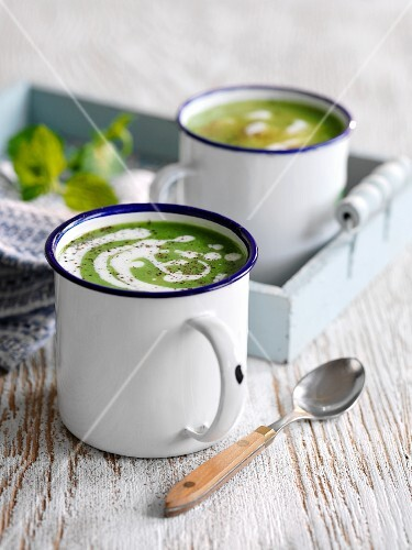 Cream of pea soup with mint in enamel mugs