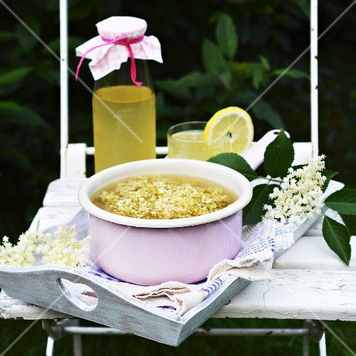 Homemade elderflower syrup in a bottle, a glass and an enamel pot on a tray
