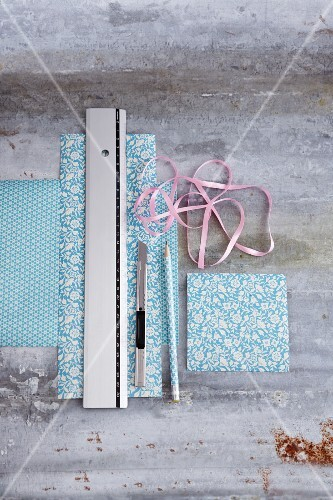 Patterned gift paper, ribbon, a ruler, a pencil and a craft knife