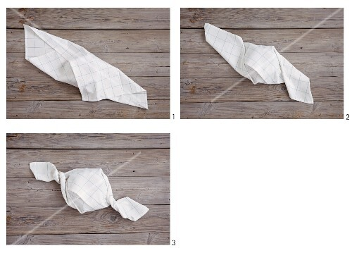A white napkin being folded into a sweet shape