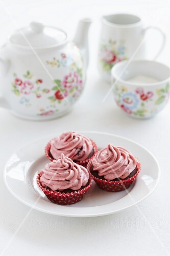 Chocolate cupcakes with raspberry frosting served with tea