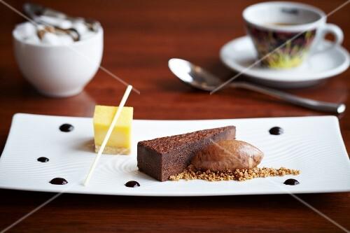A trio of desserts: chocolate torte slice, lemon tart and ice cream dumplings on a sponge base