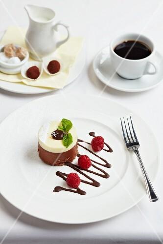 White and dark chocolate dessert with raspberries, coffee and truffle pralines