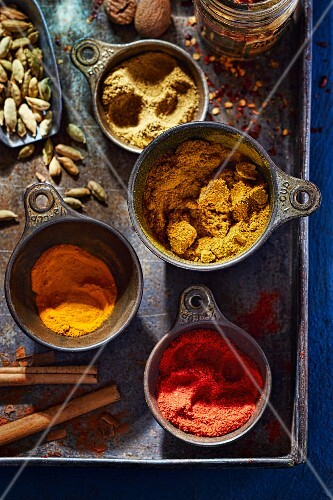 Various Indian spices in bowls on a tray
