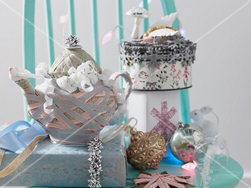 A teapot wrapped in ribbons and pastel coloured Christmas tree baubles