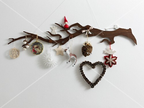 A stylised wooden twig hung with various Christmas tree decorations in natural colours