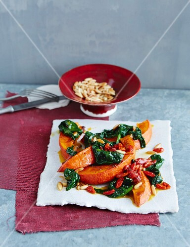 Pumpkin wedges on wilted spinach with goji berries