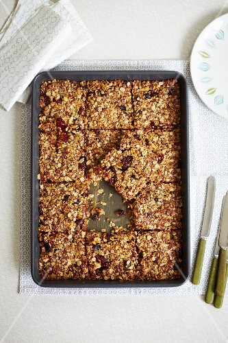 Flapjacks with cranberries and pistachios on a baking tray