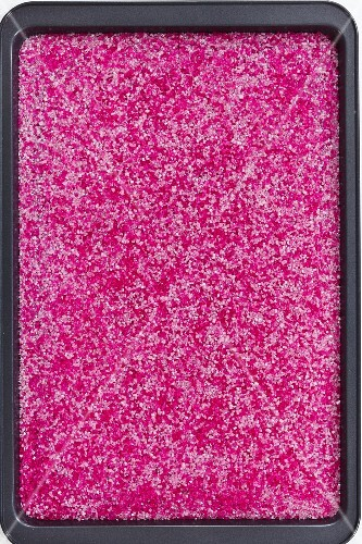 A baking tray filled with bright pink sugar nibs tthe(seen from above)