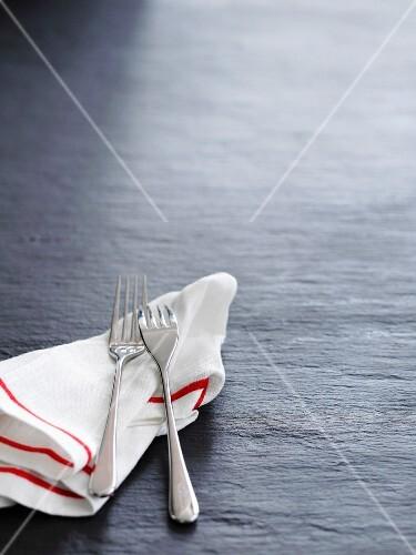 A tea towel and two forks on a slate surface