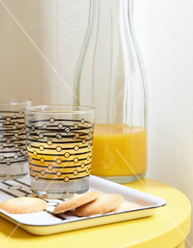 Orange juice in glasses with graphic pattern & matching tray on yellow bedside cabinet