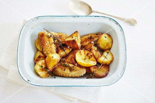 Oven-roasted potatoes and chicken wings with lemons and thyme