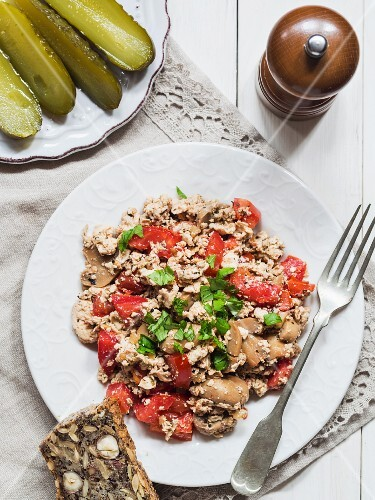 Scrambled tofu with vegetables served with flourless nut bread and gherkins