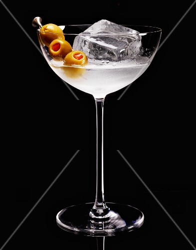 A cocktail with ice cubes and olives