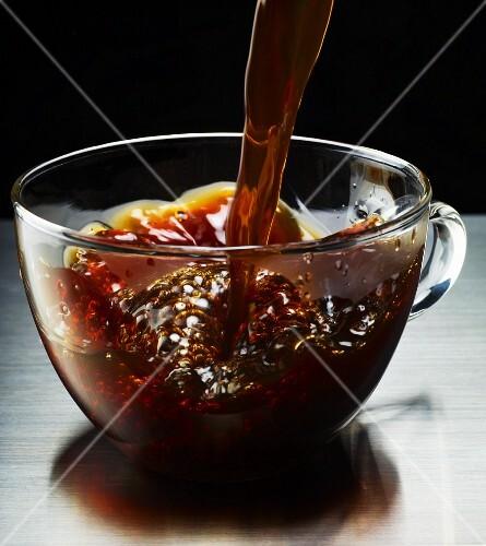 Black coffee being poured into a glass mug