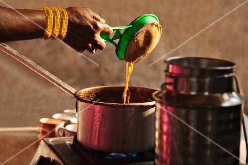 An Indian woman while preparing chai
