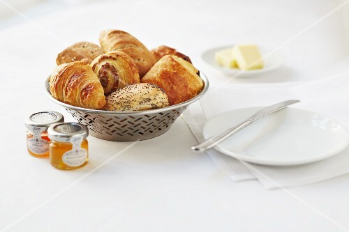 A basket of breakfast rolls, croissants, Danish pastries and poppy seed rolls with butter and jars of jam