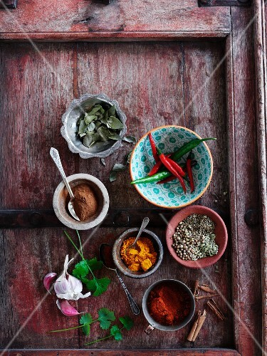 Various spices and herbs on a wooden tray