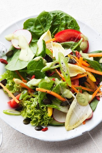 A mixed salad with vegetables and a dressing