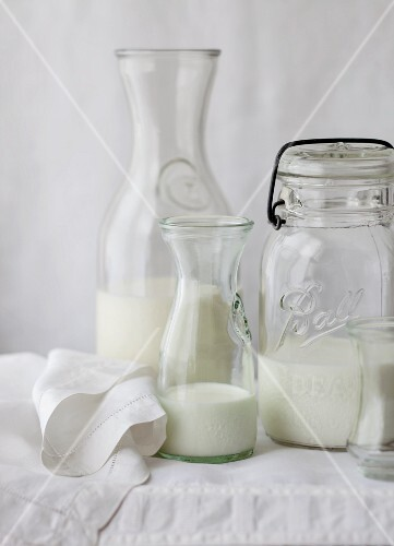 Various types of milk in different bottles on a white tablecloth
