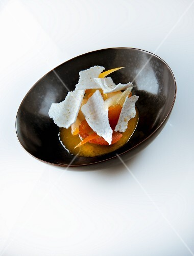 A dessert with candied citrus fruits and meringue chips