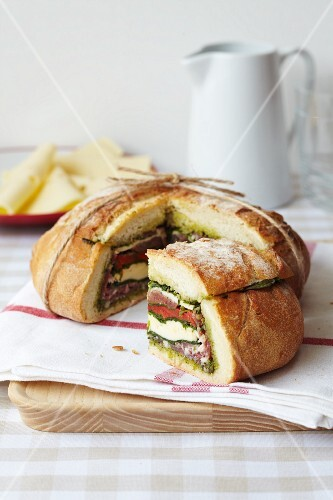 Boule filled with meat, cheese, pesto and tomatoes