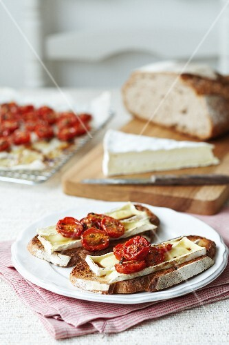 Slices of white bread topped with brie and roasted cherry tomatoes