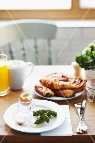 Breakfast of asparagus tips, a soft boiled egg, pain au chocolat, Danish pastry, orange juice and coffee