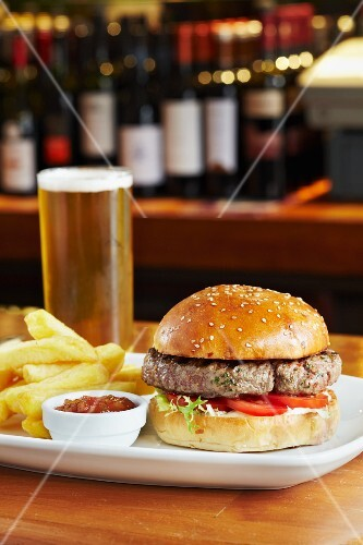 A burger with chips, tomato sauce and a pint of beer