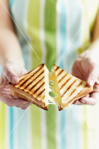 A woman breaking an toasted cheese sandwich in two