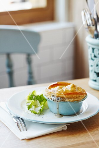 Chicken pie with a puff pastry lid and a mixed leaf salad