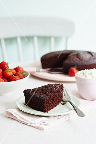 Chocolate cake served with strawberries and cream